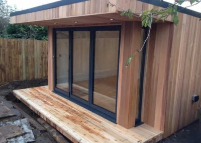 Front right angled garden room with deck and folding door