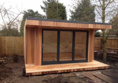 Garden room with folding door next to tree