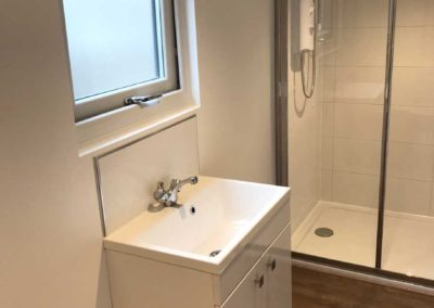 Inside garden room bathroom with sink and electric shower