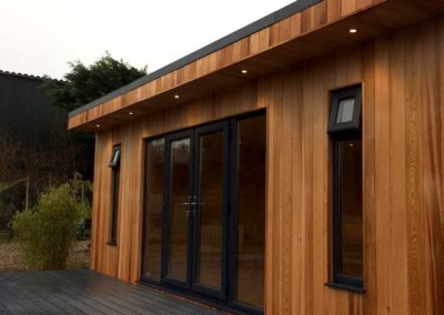 angled garden room front with grey deck and spotlights