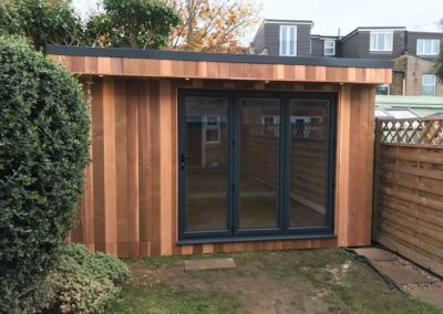 Small garden room next to fence