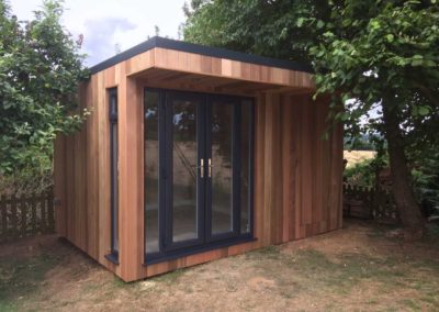Angled garden room with grey double door and blended second entrance