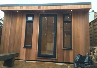 Angled garden room with single door next to bench