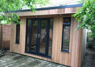 Angled garden room with grey doors and narrow windows