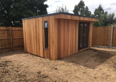 Angled garden room with double doors and narrow side window
