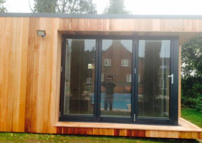 Completed garden room front with pool reflection