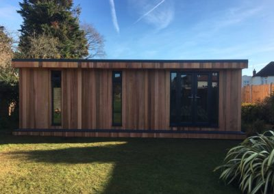 Large garden room with double door and vertical windows with grass