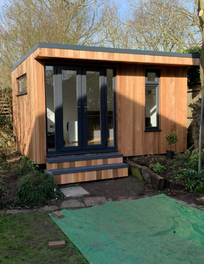 Angled small garden room with double doors and grey step deck