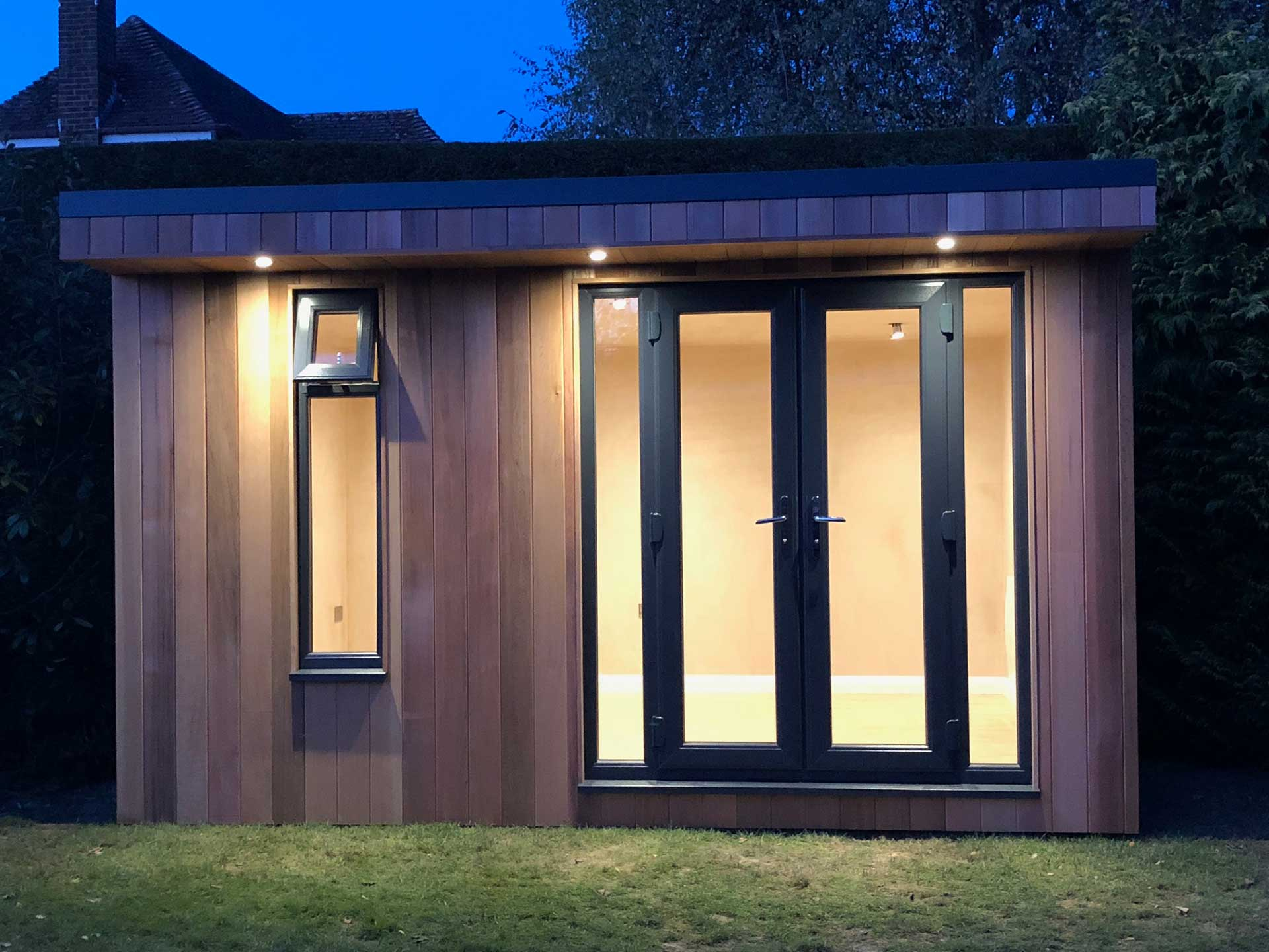 Garden room with double doors and vertical window with spotights illuminated