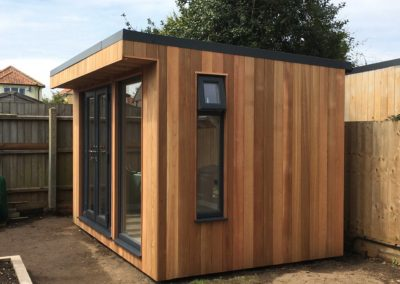 Side view of small garden room with narrow vertical window