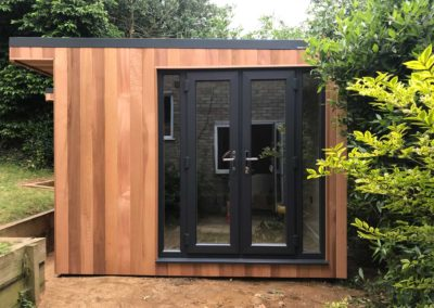 Garden room with double doors next to large bush