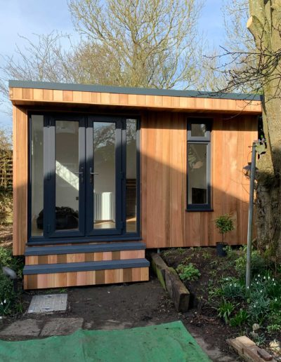 Small garden room with double doors and grey step deck