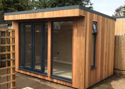 Small garden room with double doors and large window corner angle