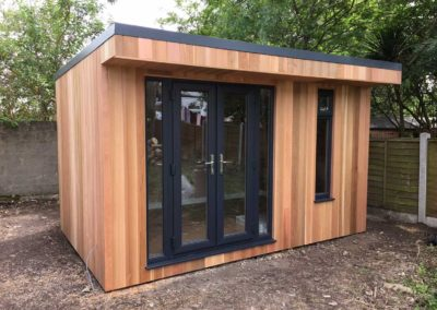 Small garden room with grey doors next to fence