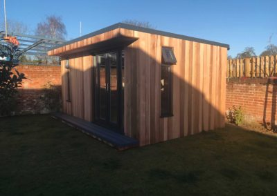 Angled garden room with double doors and side vertical window