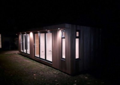 Garden room with lights on at night