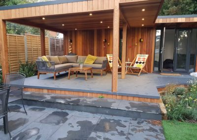 Garden room with garden furniture on large grey deck