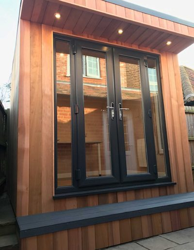 Small garden room with double doors on concrete base
