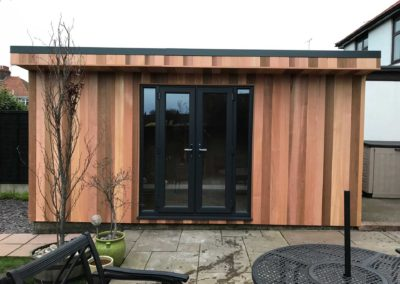 Front of small garden room on concrete base with outside furniture