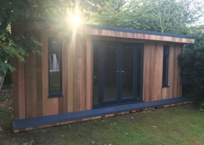 Angled garden room under trees with grey double doors