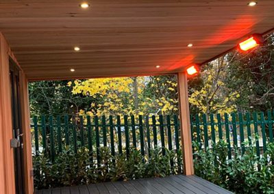 garden room with grey deck and canopy with heaters and spotlights