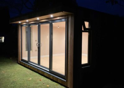 Side of garden room with interior lights illuminated